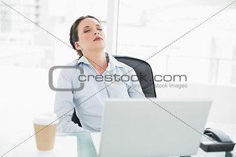 Sleepy stylish brunette businesswoman relaxing at her desk
