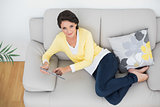 Amused casual brunette in yellow cardigan using a tablet pc