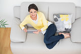 Delighted casual brunette in yellow cardigan using a tablet pc