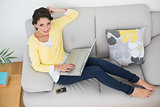 Happy casual brunette in yellow cardigan using a laptop