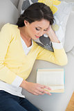 Peaceful casual brunette in yellow cardigan reading a book