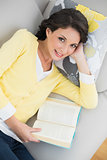Smiling casual brunette in yellow cardigan reading a book