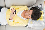 Cheerful casual brunette in yellow cardigan using a mobile phone