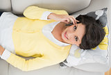 Pretty casual brunette in yellow cardigan making a phone call
