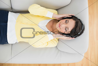 Calm casual brunette in yellow cardigan listening to music with headphones