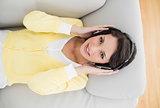 Cheerful casual brunette in yellow cardigan listening to music with headphones
