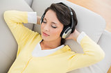 Relaxed casual brunette in yellow cardigan listening to music with headphones