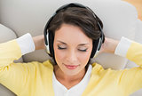 Peaceful casual brunette in yellow cardigan enjoying music