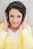 Cute casual brunette in yellow cardigan enjoying music