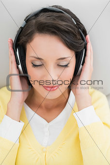 Calm casual brunette in yellow cardigan enjoying music
