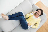 Beautiful casual brunette in yellow cardigan making a phone call