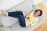 Relaxed casual brunette in yellow cardigan holding a mug of coffee