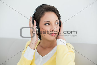 Thoughtful casual brunette in yellow cardigan listening to music with headphones