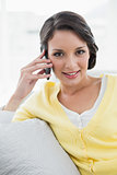 Happy casual brunette in yellow cardigan calling with her mobile phone