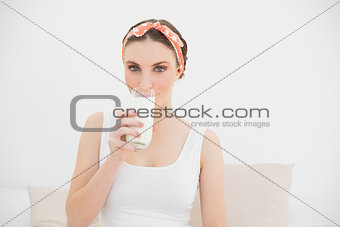 Woman drinking a glass of milk looking into the camera