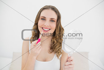 Smiling woman using lip gloss