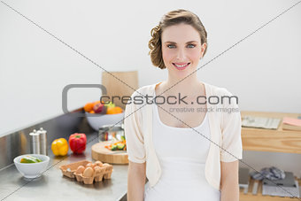 Attractive brunette woman posing in her kitchen