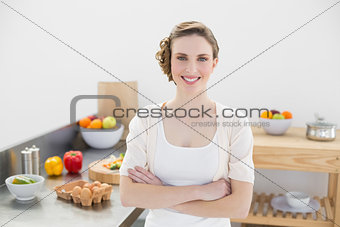 Beautiful young woman posing in her kitchen with arms crossed