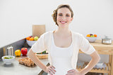 Cheerful calm woman posing in kitchen with hands on hips