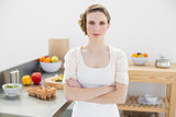 Peaceful serious woman standing with arms crossed in kitchen