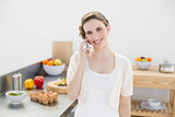 Content young woman honing while standing in kitchen