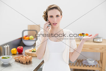 Attractive young woman discussing on the phone standing in the kitchen