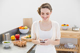Cheerful young woman messaging with her smartphone standing in the kitchen