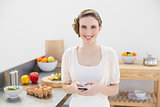 Peaceful lovely woman holding her smartphone standing in the kitchen