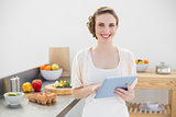 Cheerful lovely woman holding her tablet standing in her kitchen