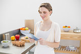 Smiling cute woman using her tablet standing in her kitchen