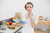 Thinking gorgeous woman standing in kitchen while holding her tablet
