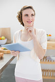 Smiling thinking woman holding her tablet standing in kitchen
