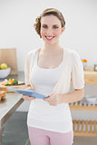 Content brunette woman holding her tablet smiling at camera