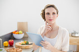 Young thoughtful woman standing in kitchen holing her tablet
