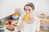 Lovely brunette woman drinking a glass of orange juice standing in her kitchen