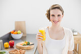 Beautiful woman posing in her kitchen holding a glass of orange juice