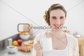 Smiling young woman posing in kitchen holding a cup