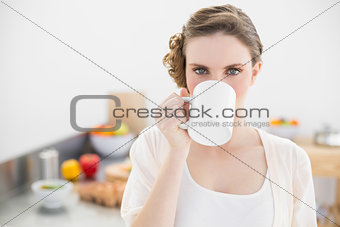 Beautiful woman drinking from cup standing in her kitchen