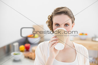 Beautiful woman drinking of disposable cup standing in kitchen