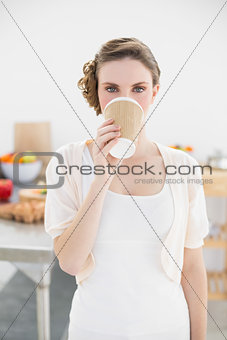 Cute woman standing in kitchen drinking of disposable cup