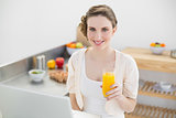 Joyful brunette woman holding a glass of orange juice while sitting in kitchen