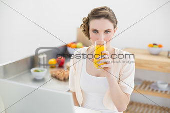 Cute woman drinking a glass of orange juice sitting in her kitchen in front of her notebook