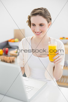 Joyful young woman looking at her laptop sitting in her kitchen