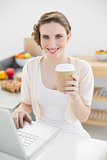 Gorgeous woman using her notebook in her kitchen holding a disposable cup