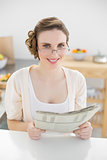 Young woman wearing glasses for reading newspaper in her kitchen