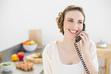 Cute peaceful woman phoning with a telephone in her kitchen