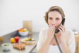 Shocked cute woman phoning in her kitchen with a telephone