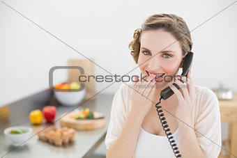 Amused lovely woman sitting in her kitchen phoning with a telephone
