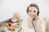 Content beautiful woman phoning in her kitchen with a telephone
