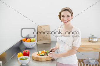 Cute woman cutting vegetables standing in her kitchen